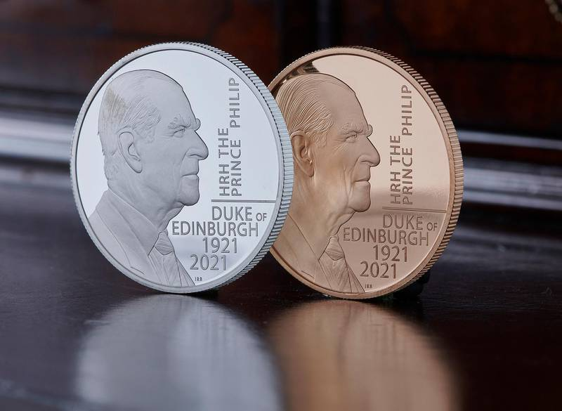This undated photo issued by HM Treasury shows the silver and gold coins commemorating the life of Prince Philip, the Duke of Edinburgh, unveiled by Chancellor Rishi Sunak on Saturday June 26, 2021. The special edition 5 pound coin features an original portrait of the Duke and the coin's design was approved by the Duke before his death. (HM Treasury via AP)