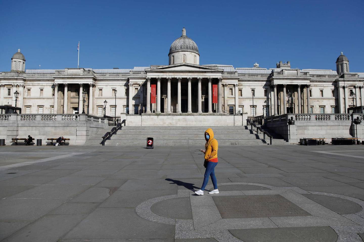 """A masked visitor walks past the National Gallery in a near deserted Trafalgar Square in central London on March 25, 2020, after Britain's government ordered a lockdown to slow the spread of the novel coronavirus. Britain was under lockdown, its population joining around 1.7 billion people around the globe ordered to stay indoors to curb the """"accelerating"""" spread of the coronavirus. / AFP / Tolga AKMEN"""