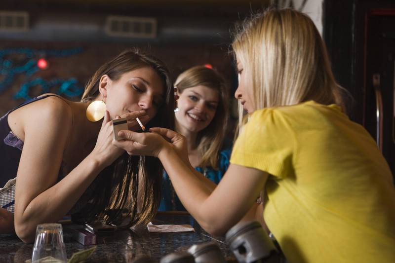 Young women lighting a cigaret --- Image by © Jimmy Collins /Corbis