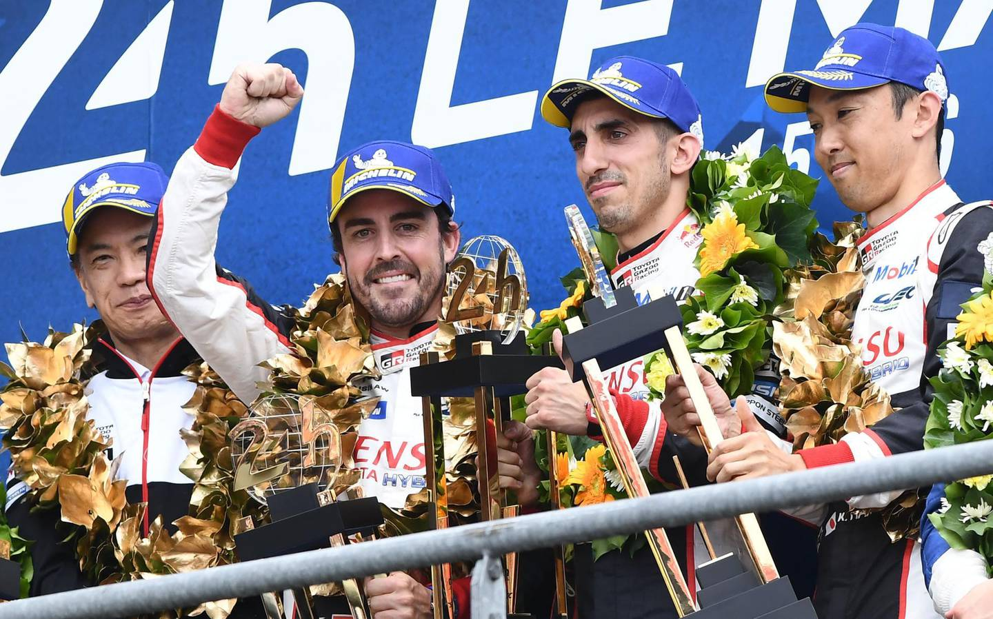 TOPSHOT - Toyota TS050 Hybrid LMP1 of Japanese's driver Kazuki Nakajima (R) Spain's driver Fernando Alonso (2L) and Switzerland's driver Sebastien Buemi (2R) celebrates on podium after winning in the 87th edition of the 24 Hours Le Mans endurance race on June 16, 2019, at Le Mans northwestern France.   / AFP / Fred TANNEAU