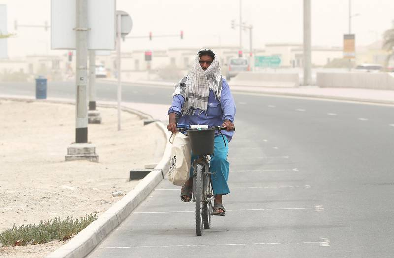DUBAI , UNITED ARAB EMIRATES , JULY 30 – 2018 :- One of the worker covering his face during the dusty and hot weather in Jumeirah Park area in Dubai. ( Pawan Singh / The National )  For News.