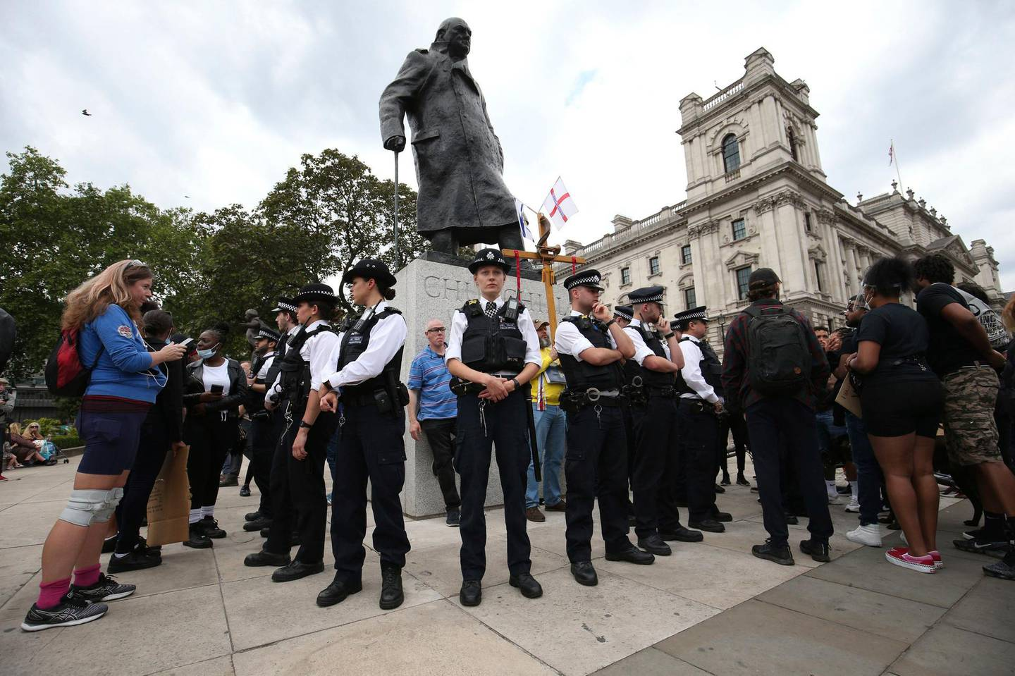 Police stand around the Winston Churchill statue ahead of a rally at the Nelson Mandela statue in the square, to commemorate George Floyd, on the day of his funeral, in Parliament Square, London, Tuesday June 9, 2020. The recent death of George Floyd who died after a U.S. officer pressed his knee into his neck, has prompted investigations into the lorded promotion of many historical figures who gave money to philanthropic enterprises, gave their names to British city areas, statues and landmarks, but gained much of their wealth from the slave trade. (Jonathan Brady/PA via AP)