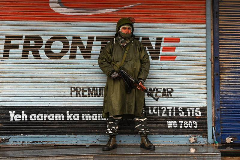 An Indian paramilitary trooper stands guard infront of closed shops during a lockdown in Srinagar on November 22, 2019. / AFP / Tauseef MUSTAFA