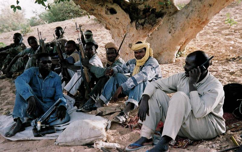 """(FILES) -- Picture taken in April 2004 shows members of the southern-based rebel Sudan People's Liberation Army (SPLA), one of them using a satphone, sitting in the forest in Sudan's western region of Darfur. The Sudanese air force bombed 04 Jun 2004 a market in Darfur, a mediator in Chad trying to bring about an end to a conflict which has sparked a serious humanitarian crisis. No casualties were reported in the bombardment. Fighting in the area that has erupted in February 2003 between the Sudanese government and Darfur rebels has claimed at least 10,000 lives and raised the spectre of a devastating humanitarian crisis that could see up to one million die, the UN and international officials have said. The pro-Sudanese government """"Janjaweed"""" militia have been accused of ethnic cleansing against the black population of the Darfur region.            AFP PHOTO/Julie FLINT (Photo by JULIE FLINT / AFP)"""
