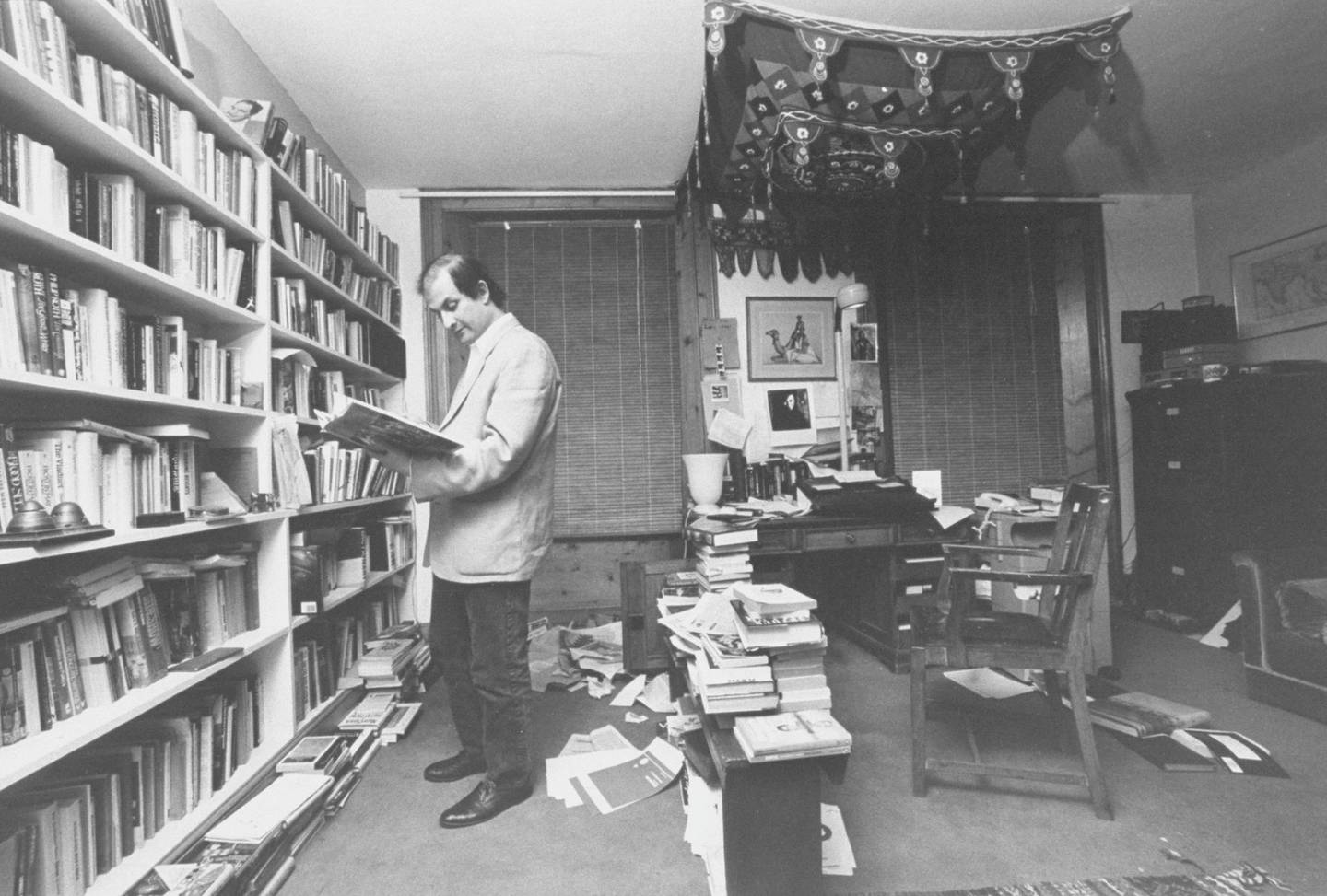 Indian Moslem writer Salman Rushdie in cluttered study going through book before going into hiding after writing SATANIC VERSES for which the Ayatollah Khomeini would soon sentence him to death.  (Photo by Terry Smith/The LIFE Images Collection via Getty Images/Getty Images)