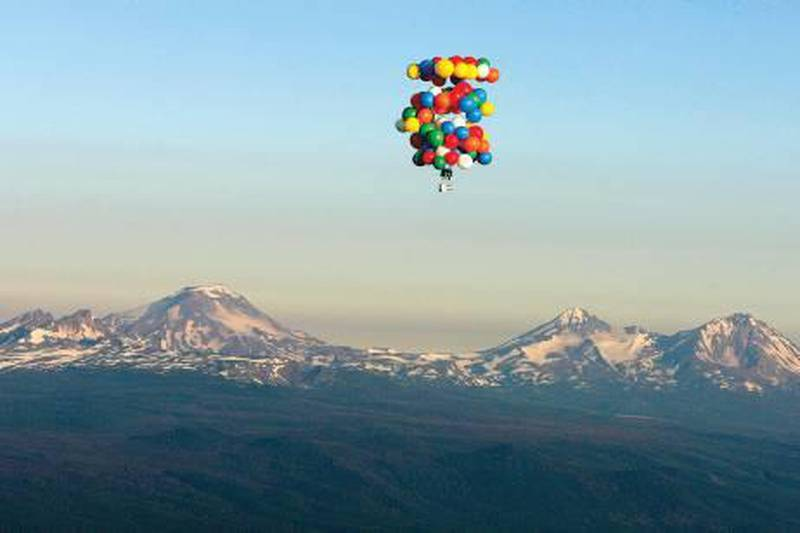 FILE -  In this July 7, 2007 file photo, cluster balloonist Kent Couch, sitting in a lawn chair, ascends past Mount Bachelor to his cruising altitude at the start of his attempt of a flight to Idaho, near Bend, Ore. Bend gas station owner Kent Couch who floated to Idaho in 2008 in a lawn chair is planning another cluster balloon adventure, in Baghdad. Couch told KTVZ he was invited by Iraqi daredevil Fareed Lafta who wants to lift off with him Nov. 15 at a Talent for Youth Conference in the Green Zone. Couch says he's working with U.S. and Iraqi military to make sure they'll be secure on what he hopes will be a flight of more than 400 miles at an elevation of 25,000 feet, using oxygen masks. (AP Photo/The Bulletin, Pete Erickson, File)