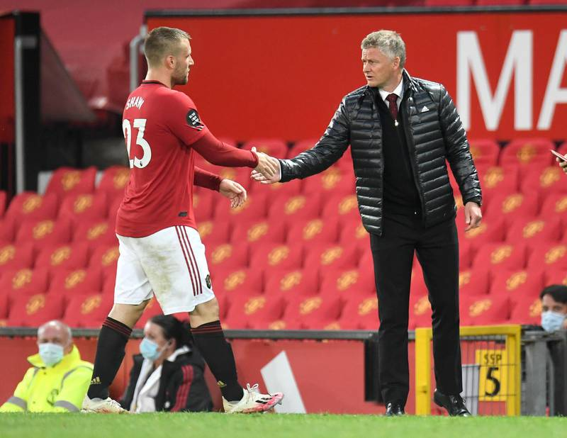 Manchester United's manager Ole Gunnar Solskjaer, right, shakes the hand of Luke Shaw as he leaves the pitch during the English Premier League soccer match between Manchester United and Southampton at Old Trafford in Manchester, England, Monday, July 13, 2020. (AP Photo/Peter Powell,Pool)