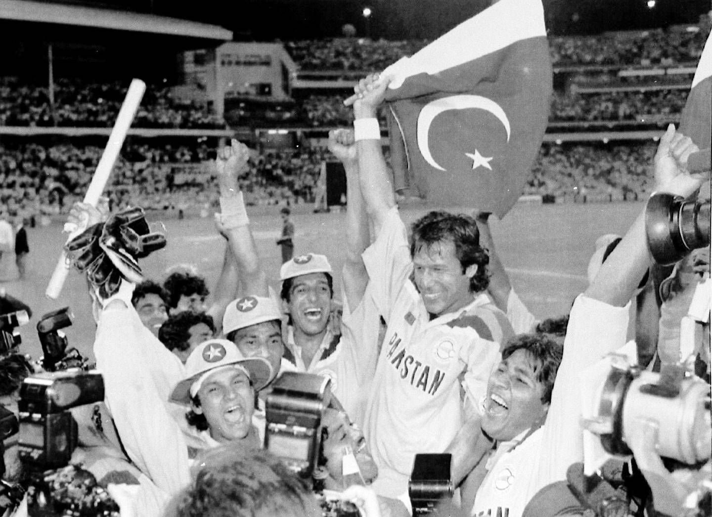 FILE - In this March 25, 1992 file photo, Pakistan's cricket captain Imran Khan, waving a Pakistan flag, is cheered by his teammates after Pakistan defeated England in the World Cup Cricket final, in Melbourne, Australia. On Thursday July 26, 2018, Khan's political party, Tehreek-e-Insaf (Movement of Justice), took a commanding lead in the Pakistan general election and he was set to become the first international cricketer in the world to be elected as a country's prime minister, considered the second toughest job in Pakistan. (AP Photo/Steve Holland, File)