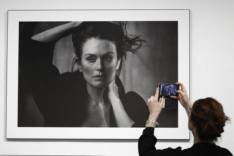 """MOSCOW, RUSSIA - MARCH 16, 2017: A woman takes a picture of a photograph of actress Julianne Moore taken for the 2017 Pirelli Calendar on display at an exhibition titled """"Pirelli Calendar 2017 by Peter Lindbergh"""" at Moscow's Multimedia Art Museum. The exhibition is open from March 17 to May 14, 2017. Artyom Geodakyan/TASS (Photo by Artyom Geodakyan\TASS via Getty Images)"""