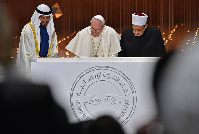 """Abu Dhabi's Crown Prince Mohammed bin Zayed al-Nahyan (L) watches as Pope Francis (C) and Egypt's Azhar Grand Imam Sheikh Ahmed al-Tayeb sign documents during the Human Fraternity Meeting at the Founders Memorial in Abu Dhabi on February 4, 2019. Pope Francis rejected """"hatred and violence"""" in the name of God, on the first visit by the head of the Catholic church to the Muslim-majority Arabian Peninsula. / AFP / Vincenzo PINTO"""