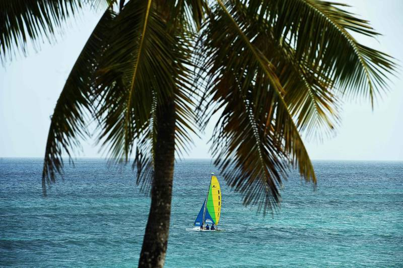 (FILES) In this file photo people sail on a boat near a beach in Bridgetown, Barbados on May 4, 2015.  Barbados has announced its intention to remove Queen Elizabeth II as head of state and become a republic by November next year, as the Caribbean island nation seeks to move fully beyond its colonial past.The decision was formalized in the so-called Throne Speech, delivered on behalf of Prime Minister Mia Mottley by the island's Governor-General Sandra Mason to mark the state opening of parliament on September 15, 2020. / AFP / Jewel SAMAD