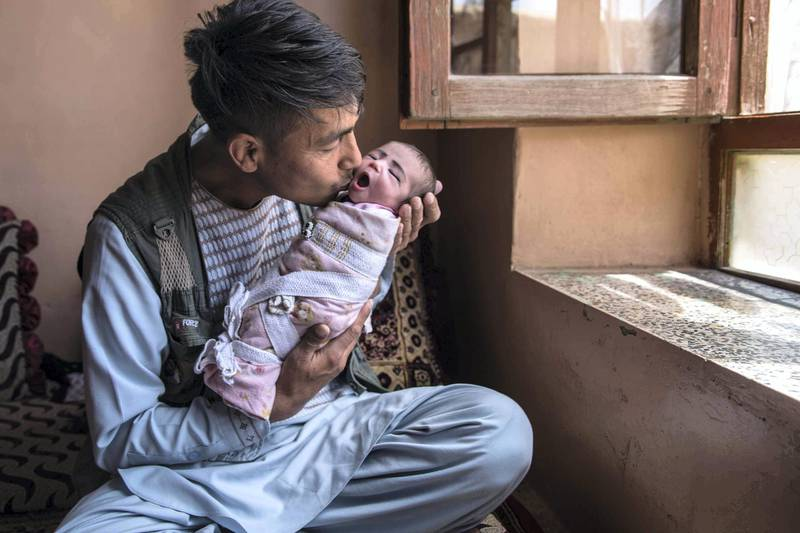 """Agha Gul, a 35-year-old father holds his newborn daughter Zahra. Now I am both your father and your mother,"""" he told her."""