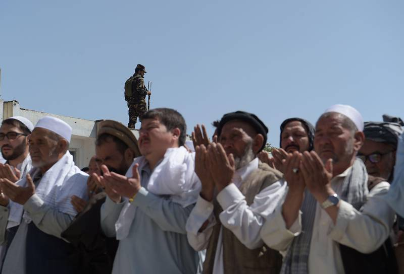 A security guard keeps watch as Afghan mourners and relatives pray in front of the coffin of one of the 28 victims of a suicide attack, on a Shiite mosque a day earlier, in Kabul on August 26, 2017. Hundreds of Shiite mourners began burying the victims of a suicide bomb and gun attack on a Kabul mosque on August 26 as the death toll from the atrocity rose to 28.Distraught relatives and friends carried coffins into the cemetery one by one, a day after the latest deadly attack claimed by the Islamic State group on Afghanistan's reeling minority Shiite community. / AFP PHOTO / SHAH MARAI
