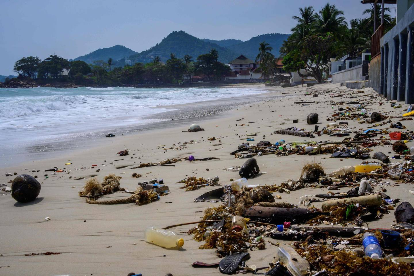 Plastic waste and other rubbish is pictured after washing up on a beach in Koh Samui in the Gulf of Thailand on January 19, 2021. / AFP / Mladen ANTONOV