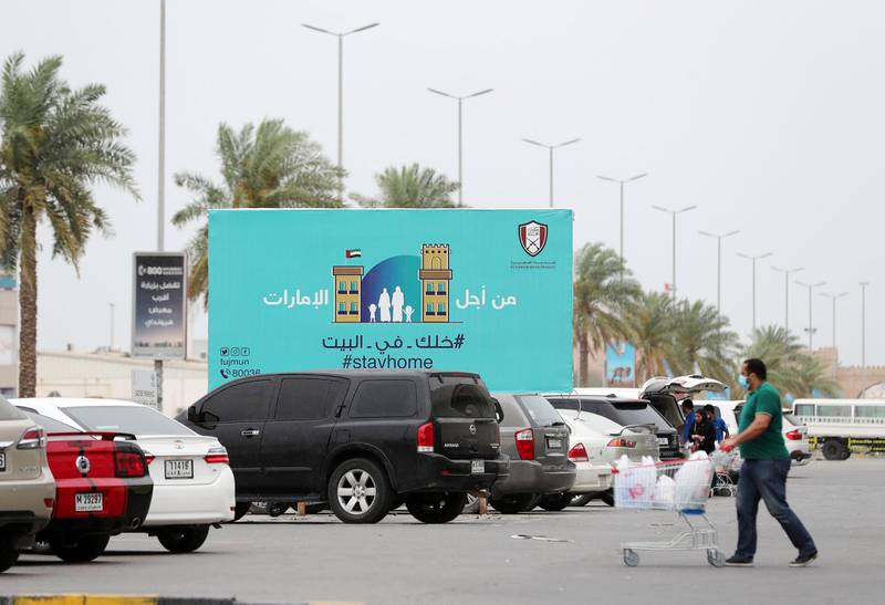 Fujairah, United Arab Emirates - Reporter: N/A: Corona. A sign in Fujairah urges people to 'Stay Home' as people do their shopping. Wednesday, April 15th, 2020. Fujairah. Chris Whiteoak / The National