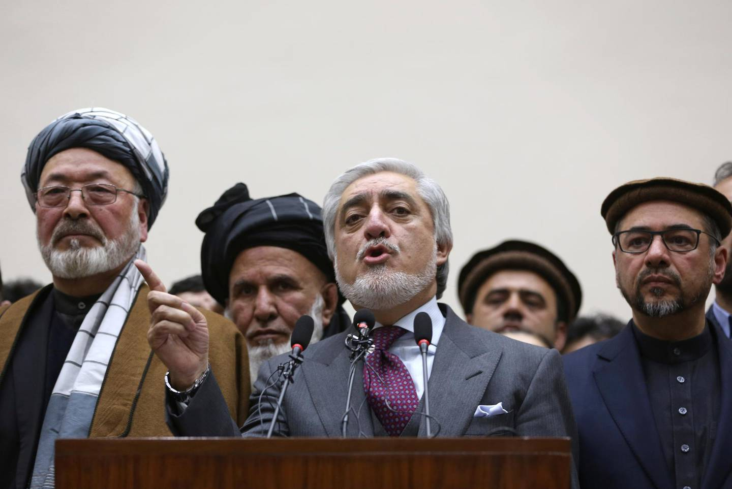 Afghan presidential candidate Abdullah Abdullah, center, addresses the media following a conference with his party members in Kabul, Afghanistan, Tuesday, Feb. 18, 2020. The country's independent election commission said Tuesday that Ashraf Ghani  won a second term as president, more than four months after polls closed. (AP Photo/Rahmat Gul)