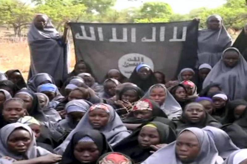 """A screengrab taken on May 12, 2014, from a video released by Nigerian Islamist extremist group Boko Haram obtained by AFP shows girls wearing the full-length hijab holding a flag reading """"There is no god, but Allah"""" and """"Mohammed is Allah's prophet"""" at an undisclosed rural location. Boko Haram released a new video on claiming to show the missing Nigerian schoolgirls, alleging they had converted to Islam and would not be released until all militant prisoners were freed.  A total of 276 girls were abducted on April 14 from the northeastern town of Chibok, in Borno state, which has a sizeable Christian community. Some 223 are still missing. AFP PHOTO / BOKO HARAM  RESTRICTED TO EDITORIAL USE - MANDATORY CREDIT """"AFP PHOTO / BOKO HARAM"""" - NO MARKETING NO ADVERTISING CAMPAIGNS - DISTRIBUTED AS A SERVICE TO CLIENTS (Photo by HO / BOKO HARAM / AFP)"""