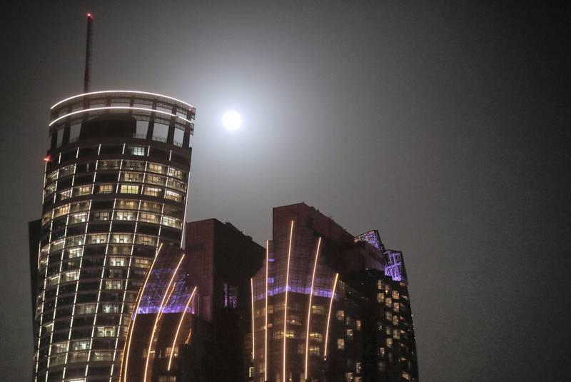 Pink Full Moon-AD  Full moon seen between the Etihad towers, Grand Hyatt Hotel & Bab Al Qasr structures in Abu Dhabi on June 24, 2021. Khushnum Bhandari/ The National Reporter: N/A News