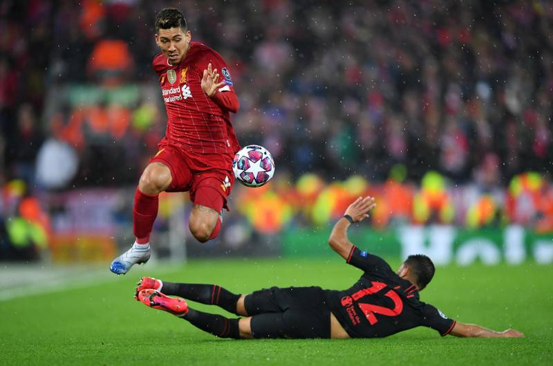 LIVERPOOL, ENGLAND - MARCH 11: Roberto Firmino of Liverpool is challenged by Renan Lodi of Atletico Madrid during the UEFA Champions League round of 16 second leg match between Liverpool FC and Atletico Madrid at Anfield on March 11, 2020 in Liverpool, United Kingdom.  (Photo by Laurence Griffiths/Getty Images)