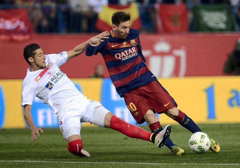 """Sevilla's defender Sergio Escudero (L) vies with  Barcelona's Argentinian forward Lionel Messi during the Spanish """"Copa del Rey"""" (King's Cup) final match FC Barcelona vs Sevilla FC at the Vicente Calderon stadium in Madrid on May 22, 2016. (Photo by CRISTINA QUICLER / AFP)"""