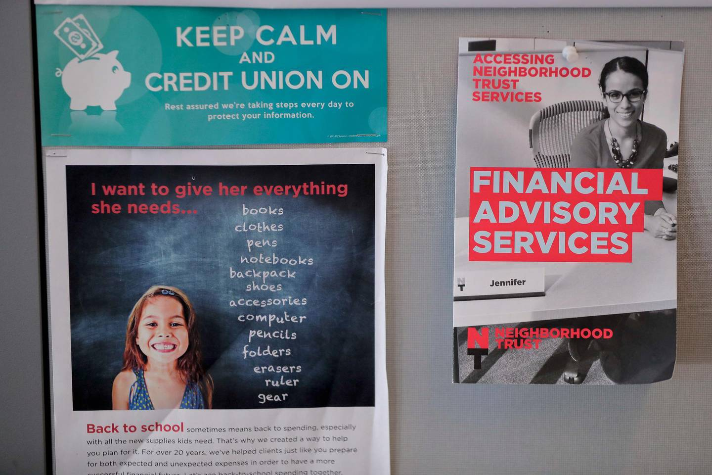 In this May 24, 2018, photo, fliers offering financial advising services to clients hang in a cubicle at the Neighborhood Trust Federal Credit Union in Washington Heights in New York. The credit union is offering services through a developing partnership with Finhabits, a bilingual digital platform designed to make savings and investment accessible for Hispanics. (AP Photo/Julie Jacobson)