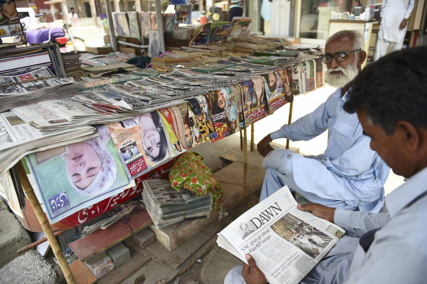 A Pakistan man reads a copy of the Dawn English-language newspaper at a newspaper stall in Karachi on May 20, 2018.  International media watchdog Reporters Without Borders (RSF) has condemned the disruption in distribution of Pakistan's oldest newspaper Dawn after it published an interview suggesting that Pakistani militants were behind the 2008 Mumbai attacks. / AFP PHOTO / RIZWAN TABASSUM