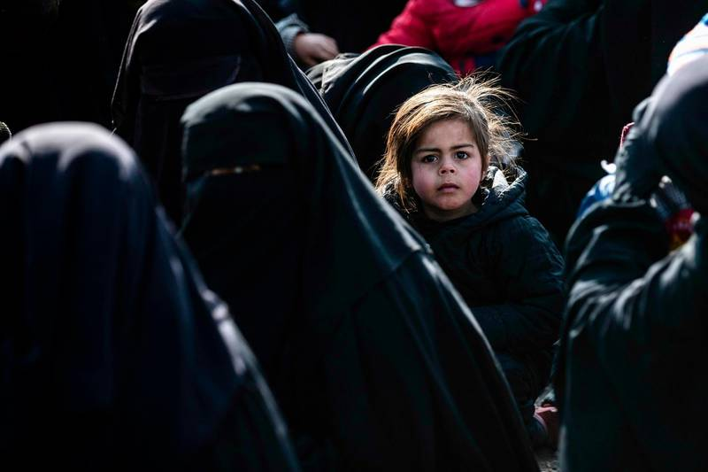 TOPSHOT - Women lead children ahead of departure during the release of another group of Syrian families from the Kurdish-run al-Hol camp which holds suspected relatives of Islamic State (IS) group fighters, in Hasakeh governorate in northeastern Syria, on January 28, 2021. / AFP / Delil SOULEIMAN