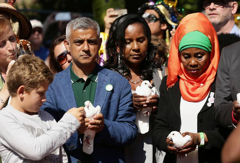 Mayor of London, Sadiq Khan, 2nd left, takes part with others in a release of doves as a show of respect for those who died in the Grenfell Tower fire, during the Notting Hill Carnival Family Day in west London, Sunday Aug. 27, 2017. (Yui Mok/PA via AP)