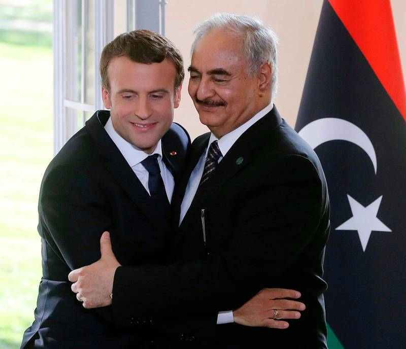 """French President Emmanuel Macron and General Khalifa Haftar, commander in the Libyan National Army (LNA) attend a press conference after talks aimed at easing tensions in Libya, in La Celle-Saint-Cloud, near Paris, on July 25, 2017. The two main rivals in conflict-ridden Libya are committed to a ceasefire and holding elections """"as soon as possible"""", according to a draft statement released ahead of French-brokered talks today. The communique says Libya's UN-backed Prime Minister Fayez al-Sarraj and Khalifa Haftar, the military commander who controls the remote east of the vast country, accept that only a political solution can end the crisis.  / AFP PHOTO / JACQUES DEMARTHON"""