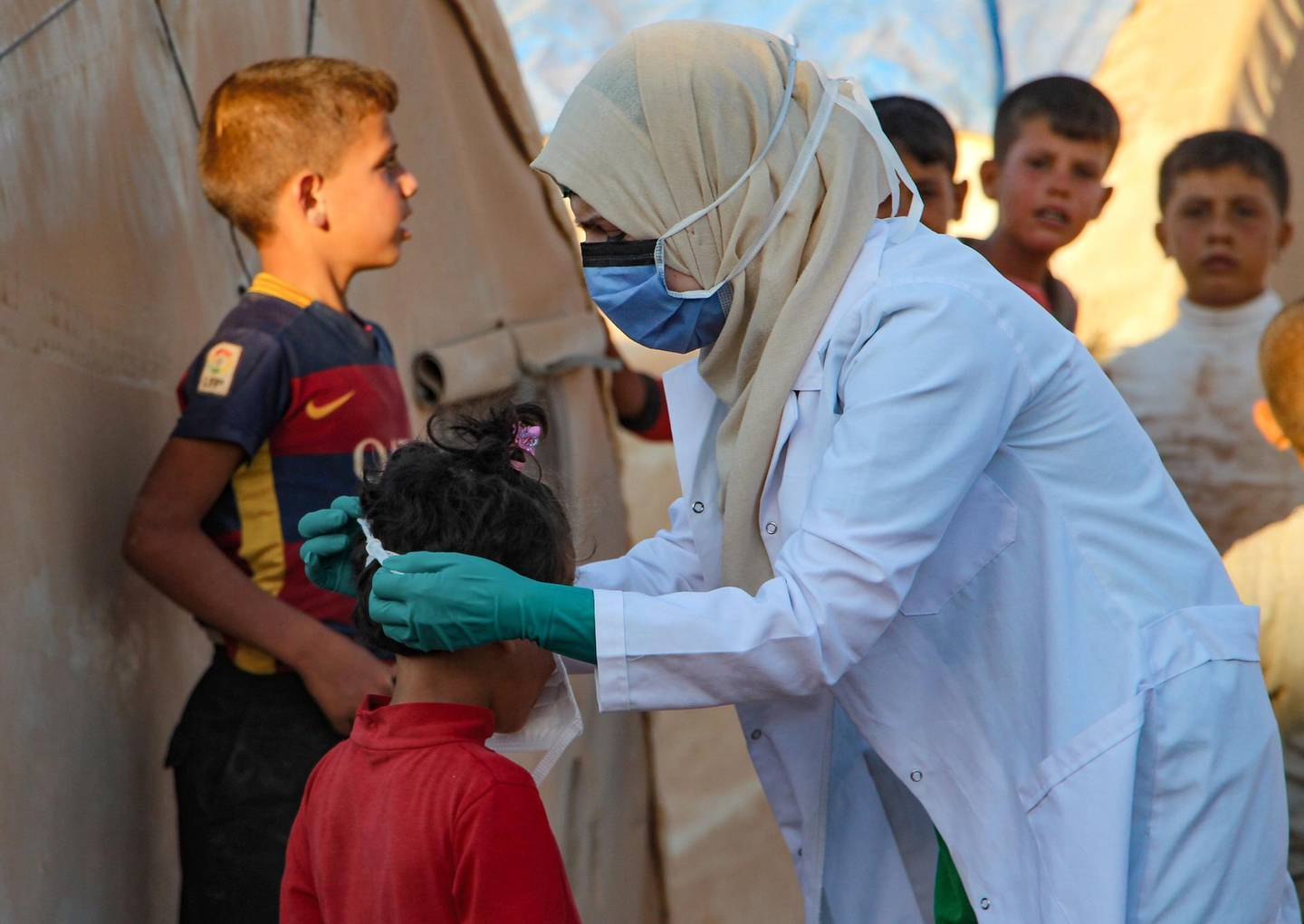 A Syrian doctor, on her own initiative, instructs children how to properly wear a mask during the novel coronavirus pandemic crisis, in the displacement camp of Janid near the town of Dana, east of the Turkish-Syrian border in the northwestern Idlib province, on July 26, 2020.   / AFP / Ibrahim YASOUF