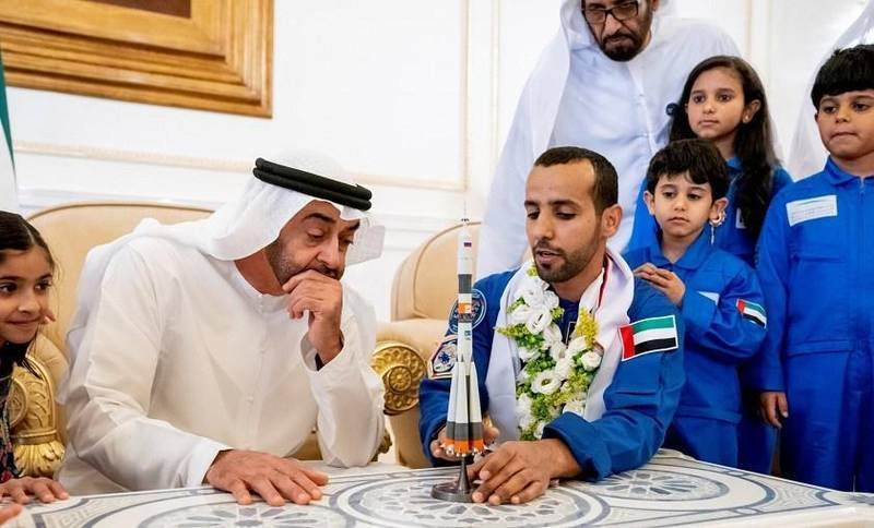 rABU DHABI, UNITED ARAB EMIRATES - October 12, 2019: HH Sheikh Mohamed bin Zayed Al Nahyan, Crown Prince of Abu Dhabi and Deputy Supreme Commander of the UAE Armed Forces (2nd L) looks at a model of the Soyuz MS-15 space ship which launched Hazza Ali Al Mansoori, the first UAE Astronaut (3rd L) to the International Space Station, during a homecoming reception at the Presidential Airport.  ( Hamad Al Kaabi / Ministry of Presidential Affairs ) ---