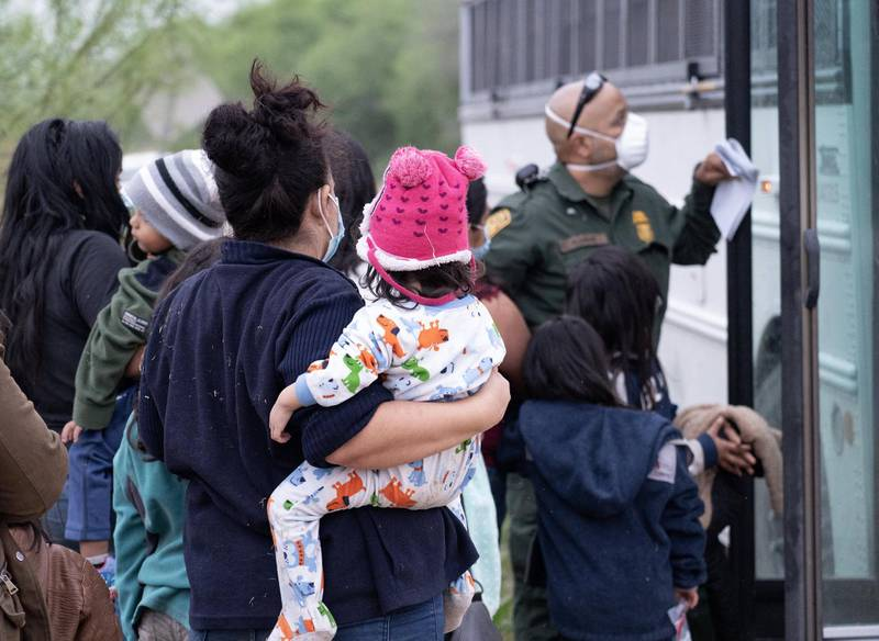 A woman holds a young girl as she's about to board a US Border Patrol bus. The vast majority of migrants apprehended by US border patrol are returned to Mexico immediately under Title 42. Willy Lowry/ The National