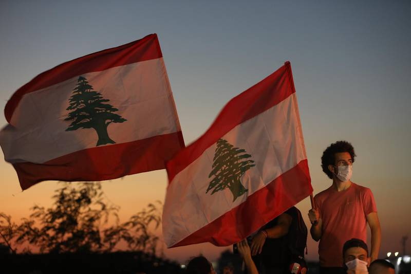 BEIRUT, LEBANON - OCTOBER 17: People wave Lebanese flags and chant to mark the one-year anniversary of anti-government protests on October 17, 2020 in Beirut, Lebanon. On the one year anniversary since the unprecedented mass protests of Lebanese demanding political change as the country buckled under social and economic devastation, Beirut remains in rubble after the August 4 port blast. (Photo by Marwan Tahtah/Getty Images)