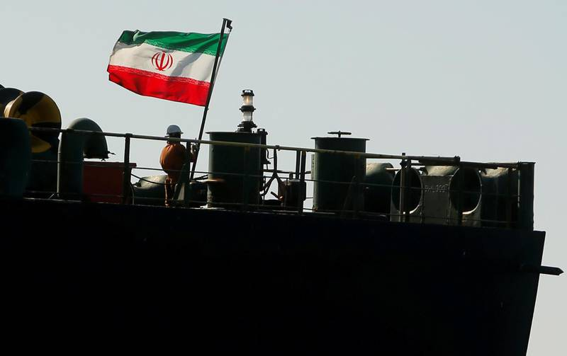REFILE - CORRECTING GRAMMAR  A crew member raises the Iranian flag on Iranian oil tanker Adrian Darya 1, previously named Grace 1, as it sits anchored after the Supreme Court of the British territory lifted its detention order, in the Strait of Gibraltar, Spain, August 18, 2019. REUTERS/Jon Nazca