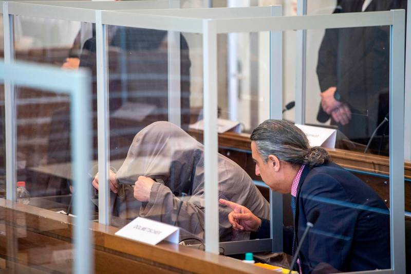 Syrian defendant Eyad al-Gharib (L) hides himself under his hood prior to a trial against two Syrian defendants accused of state-sponsored torture in Syria, on April 23, 2020 in Koblenz, western Germany. Two alleged former Syrian intelligence officers go on trial, accused of crimes against humanity in the first court case worldwide over state-sponsored torture by Bashar al-Assad's regime. Prime suspect Anwar Raslan, an alleged former colonel in Syrian state security, stands accused of carrying out crimes against humanity while in charge of the Al-Khatib detention centre in Damascus between April 29, 2011 and September 7, 2012. Fellow defendant Eyad al-Gharib, 43, is accused of being an accomplice to crimes against humanity, having helped to arrest protesters and deliver them to Al-Khatib in the autumn of 2011.  / AFP / POOL / Thomas Lohnes
