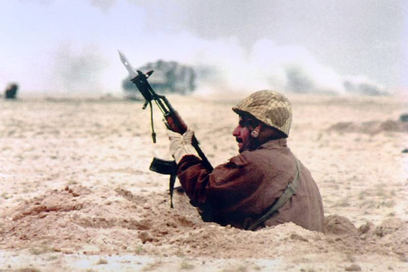An Egyptian soldier holding a bayonet takes shelter in a hole to protect himself from Iraqi artillery fire on February 25, 1991 while Allied troops launch a ground offensive to free Kuwait from Iraqi invasion . (Photo by Pascal GUYOT / AFP)