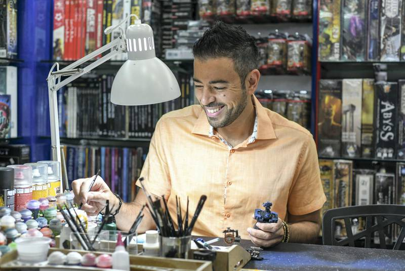 Abu Dhabi, United Arab Emirates - Mark Azzam, founder of Back to Games at the hobby painting station in the store at Al Wahda mall. Khushnum Bhandari for The National