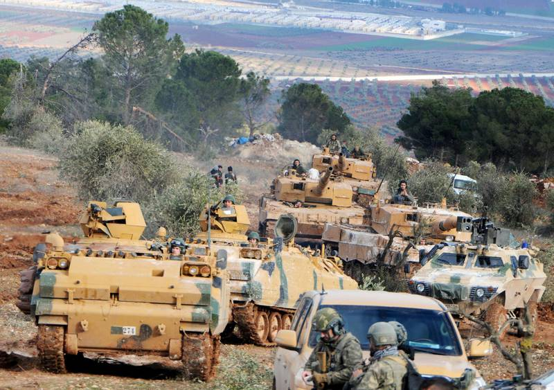 FILE - This Jan. 28, 2018 file photo, Turkish troops take control of Bursayah hill, which separates the Kurdish-held enclave of Afrin from the Turkey-controlled town of Azaz, Syria. Nearly a month into Turkey's offensive in the Syrian Kurdish enclave of Afrin, hundreds of thousands of Syrians are hiding from bombs and airstrikes in caves and basements, trapped while Turkish troops and their allies are bogged down in fierce ground battles against formidable opponents. (DHA-Depo Photos via AP, File)