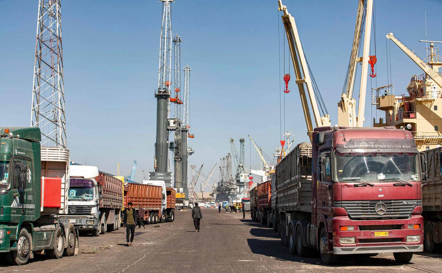 This picture taken on March 14, 2021 shows a view of trucks parked along ships on a pier at the port of Umm Qasr, south of Iraq's southern city of Basra. Iraq is ranked the 21st most corrupt country by Transparency International. In January, the advocacy group said public corruption had deprived Iraqis of basic rights and services, including water, health care, electricity and jobs. It said systemic graft was eating away at Iraqis' hopes for the future, pushing growing numbers to try to emigrate. In 2019, hundreds of thousands of protesters flooded Iraqi cities, first railing against poor public services, then explicitly accusing politicians of plundering resources meant for the people. / AFP / Hussein FALEH