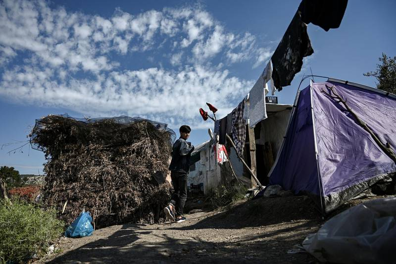A boy walks in a improvised tents camp near the refugee camp of Moria in the island of Lesbos on June 21, 2020. - Greece's announcement that it was extending the coronavirus lockdown at its migrant camps until July 5, cancelling plans to lift the measures on June 22, coincided with World Refugee Day on June 27, 2020. (Photo by ARIS MESSINIS / AFP)