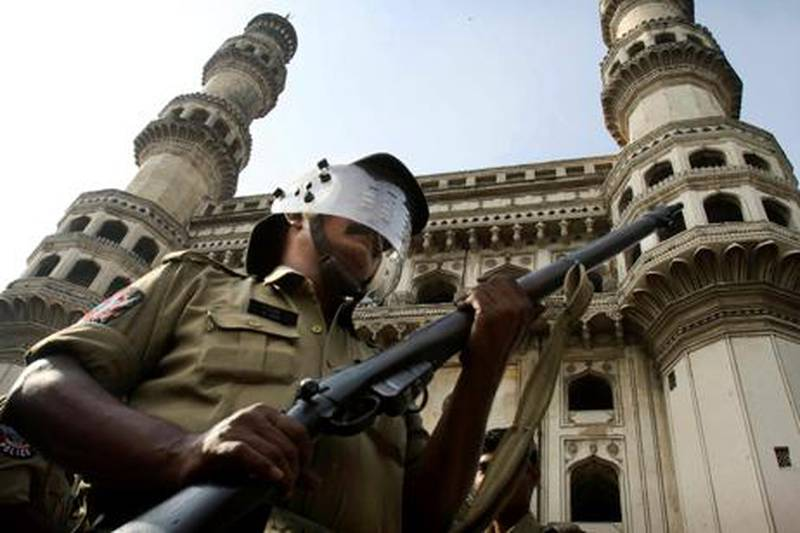 An Indian policeman stands guard in front of the landmark Charminar, ahead of a potentially explosive court verdict on whether Hindus or Muslims should control a disputed holy site in Ayodhya, in Hyderabad, India, Thursday, Sept. 30, 2010. Police have arrested more than 10,000 people to prevent them from inciting violence, while another 100,000 had to sign affidavits saying they would not cause trouble after the verdict, a top official said. A 16th-century Babri Mosque, Hindus claim was erected at the birthplace of their god Rama, stood at the disputed site in the town of Ayodhya before it was razed by Hindu hard-liners in 1992, setting off violence that killed 2,000 nationwide. (AP Photo/Mahesh Kumar A.)