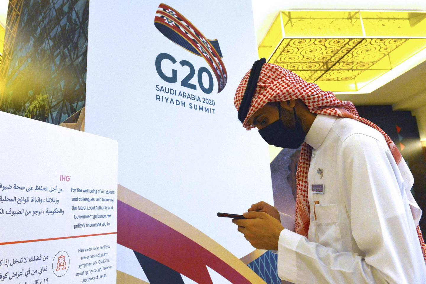 A Saudi man is pictured checks his phone as preparations take place ahead of a meeting of Finance ministers and central bank governors of the G20 nations in the Saudi capital Riyadh on November 18, 2020.  Saudi Arabia hosts the G20 summit Saturday in a first for an Arab nation, but the scaled-down virtual format could limit debate on a resurgent coronavirus pandemic and crippling economic crisis. / AFP / FAYEZ NURELDINE