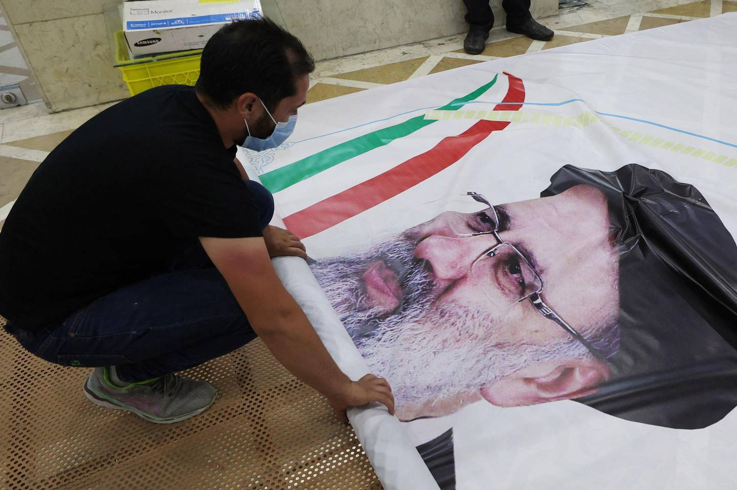 A worker prepares a campaign banner of presidential candidate Ebrahim Raisi at a print shop in the Iranian capital Tehran on June 7, 2021. Iranians are set to elect a successor to President Hassan Rouhani on June 18 amid widespread discontent over a deep economic and social crisis caused by the reimposition of crippling sanctions after the US pulled out of the 2015 nuclear deal. / AFP / ATTA KENARE