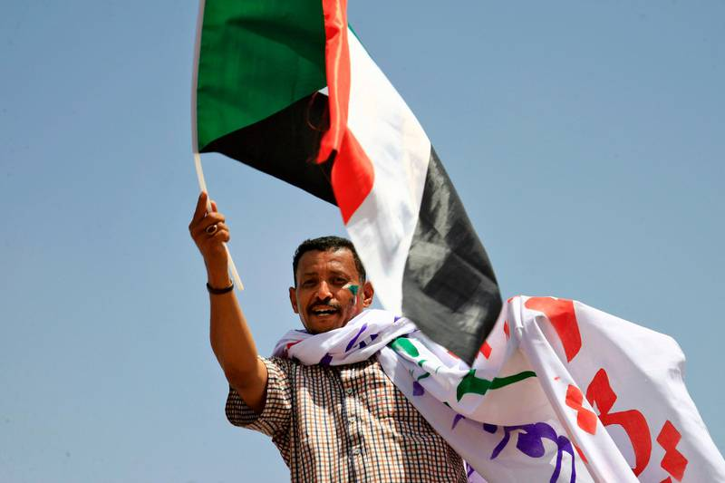 A Sudanese opposition supporter waves a national flag during a sit-in outside the army headquarters in Khartoum on May 5, 2019, as thousands of protesters remain encamped in the area to demand the current 10-member army council that took power after the ouster of the country's former president be replaced by a civilian administration. Sudanese mediators facilitating talks between the army rulers and protest leaders have proposed the country have two transition councils, with one led by generals overseeing security, according to a senior opposition leader and member of the umbrella protest group the Alliance for Freedom and Change. / AFP / ASHRAF SHAZLY