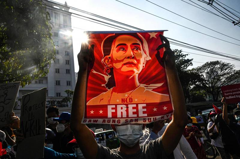 (FILES) In this file photo taken on February 15, 2021, a protester holds up a poster featuring Aung San Suu Kyi during a demonstration against the military coup in front of the Central Bank of Myanmar in Yangon. Myanmar's deposed leader Aung San Suu Kyi has been hit with fresh corruption charges, state-run media reported on June 10, 2021. -   / AFP / STR