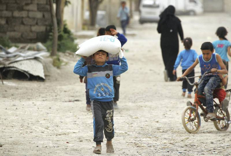 A boy carries food aid given by UN's World Food Programme in Raqqa, Syria April 26, 2018. REUTERS/Aboud Hamam