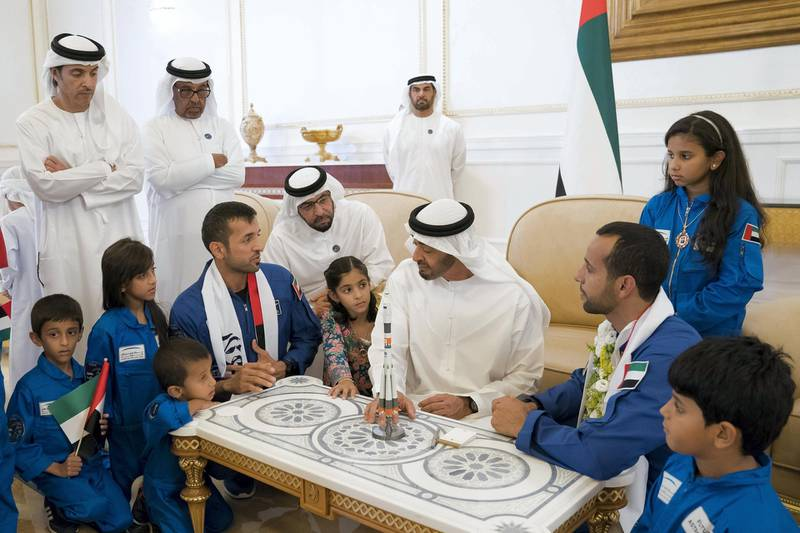 ABU DHABI, UNITED ARAB EMIRATES - October 12, 2019: HH Sheikh Mohamed bin Zayed Al Nahyan, Crown Prince of Abu Dhabi and Deputy Supreme Commander of the UAE Armed Forces (C), speaks with Sultan Saif Al Neyadi, a member of the International Space Station (ISS) mission back-up team (L) and Hazza Ali Al Mansoori, the first UAE Astronaut to be deployed on a space mission to the International Space Station (ISS) (R) , during a homecoming reception at the Presidential Airport.  Seen with HH Sheikh Hazza bin Zayed Al Nahyan, Vice Chairman of the Abu Dhabi Executive Council (back L).   ( Mohamed Al Hammadi / Ministry of Presidential Affairs ) ---