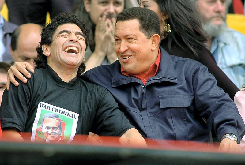 """Venezuelan President Hugo Chavez (R) jokes with Argentinian former soccer star Diego Armando Maradona during the """"People's Summit"""" massive rally against the IV Summit of the Americas, in Mar del Plata's stadium 04 November 2005. During the rally, activists will stress their opposition to the Free Trade Area of the Americas (ALCA, in spanish) and the visit of US President George W. Bush. On arrival in Mar del Plata, Chavez said """"the FTAA is dead and we are going to bury it here."""" (Photo by STR / AFP)"""