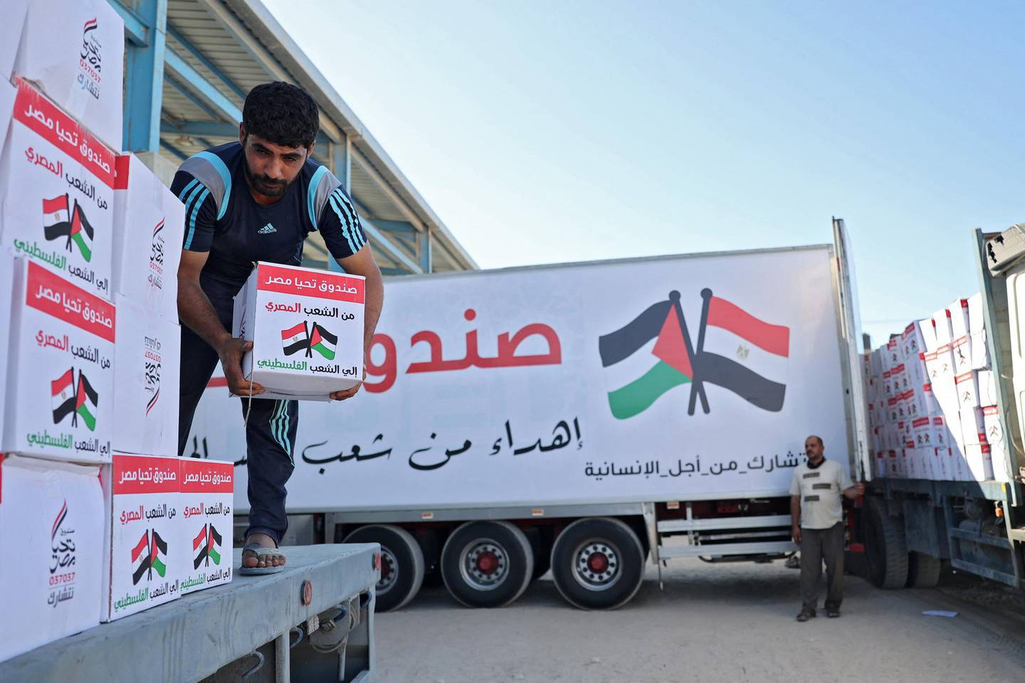 A Palestinian labourer empties boxes of aid from an Egyptian aid truck at the Rafah border crossing, which connects the Gaza Strip to Egypt, on May 23, 2021.  / AFP / SAID KHATIB