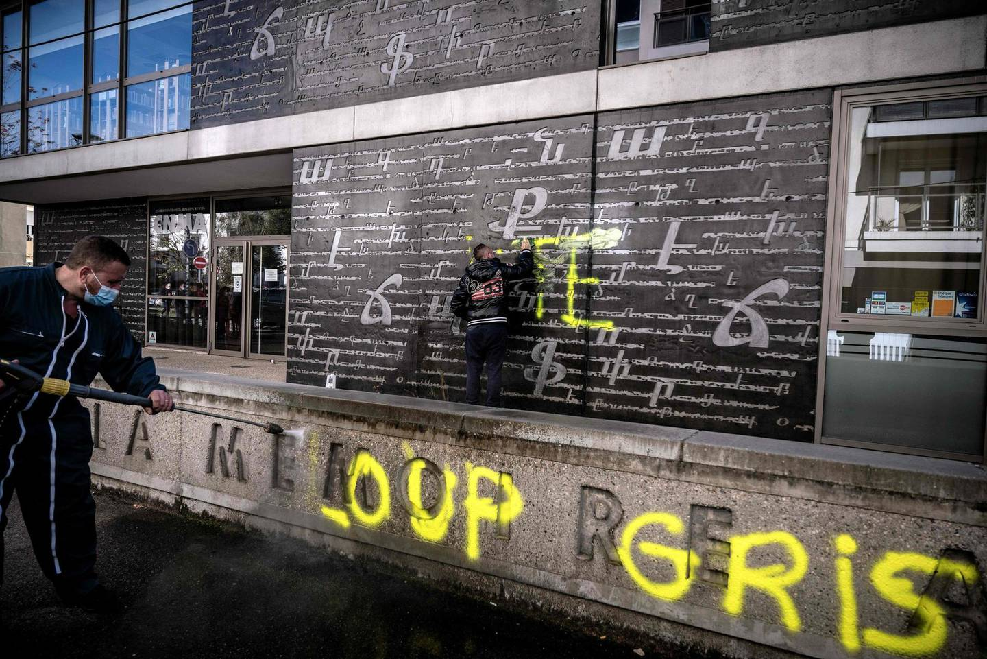 """Men clean an outside wall of the National Armenian Memorial Centre in Decines-Charpieu, near Lyon, on November 1, 2020 where pro-Turkish yellow letters graffiti tags have been painted overnight. Inscriptions read """"RTE"""" which can refers to Turkish Prime minister Recep Tayyip Erdogan and """"Grey Wolf"""" (Loup Gris), the name of an ultra-nationalist movement in Turkey. A nearby memorial for the Armenian genocide have also been tagged with the words """"Fuck Armenia"""". / AFP / JEFF PACHOUD"""